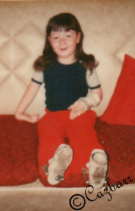 Me as a child sitting on a sofa with left hand in a splint to straighten wrist caused by Arthrogryposis