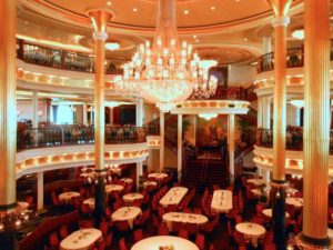 Cruising As A Wheelchair User:  Is It The Best Holiday? - Main dining hall - Big glass chandelier above table and chairs with white table cloths