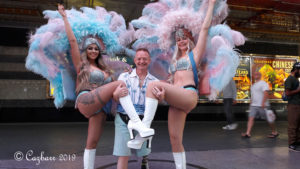 Jeff in between 2 showirls with blue feather headdresses