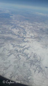 View from airplane of mountains covered with snow